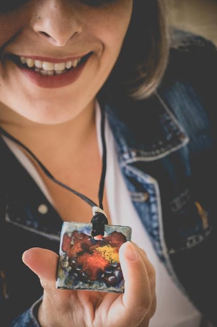 Mulher sorrindo mostrando colar de cerâmica colorido