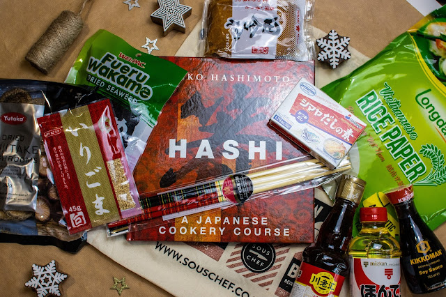 A cookbook called Hashi: a japanese cookery course surrounded by packages of various Japanese ingredients