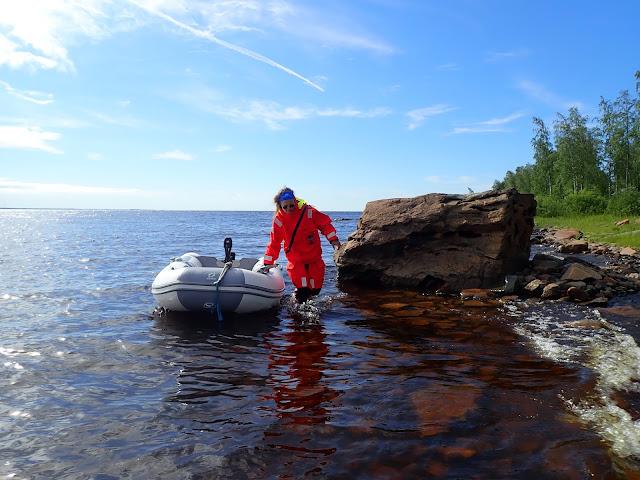 Pelastautumispukuinen henkilö vetää kumivenettä matalassa rantavedessä.