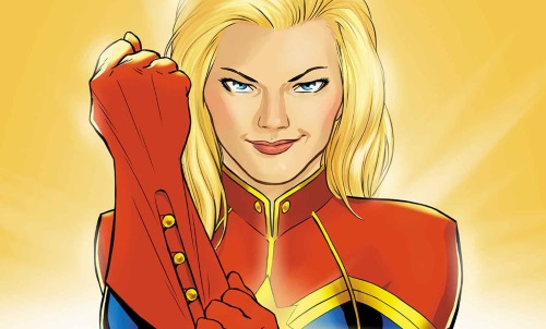 Carol Danvers, a white blonde woman, stares directly at the viewer as she pulls on a red glove with gold buttons. She wears a red, gold, and blue costume of vaguely military cut.