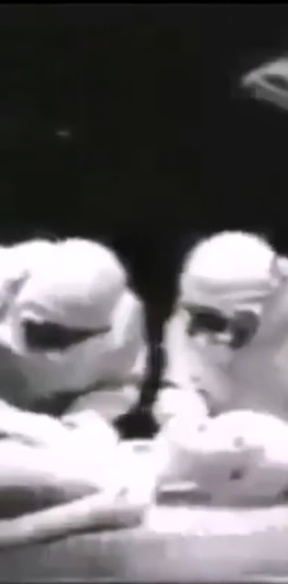 Two medics seem to be performing an autopsy on an Extraterrestrial entity.