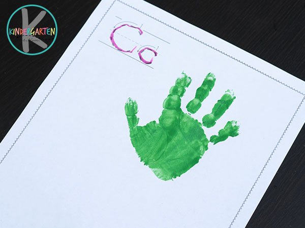 press green painted hand on paper to make the top of the carrot handprint art