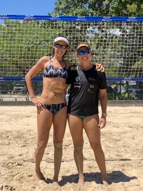 Rebecca e Talita pousam para foto na areia, com rede ao fundo
