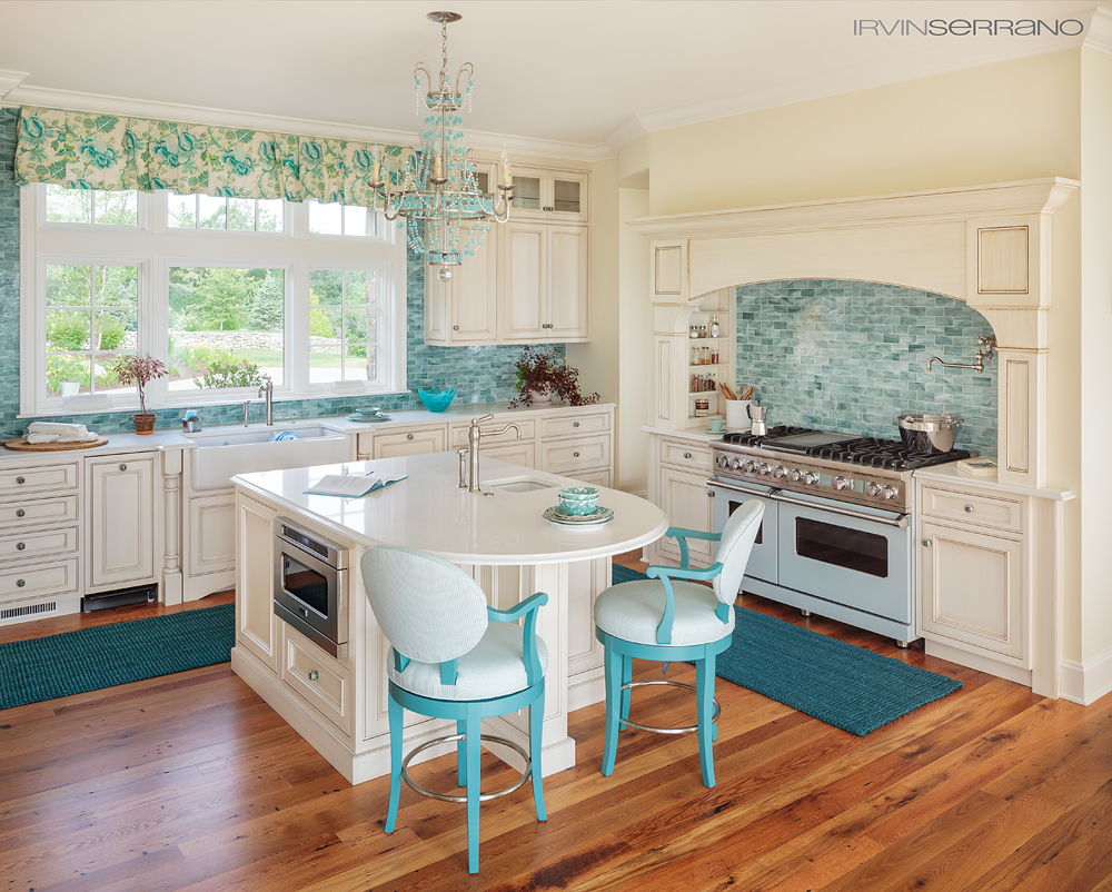 The kitchen design of an oceanview home built by Bowley Builders is accented with teal tile and chairs.