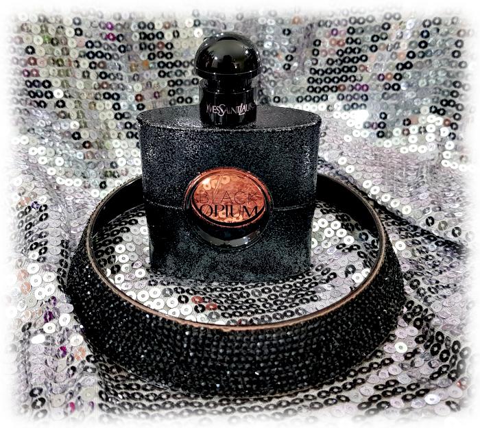 Black Opium bottle & black sequinned choker on silver sequinned background