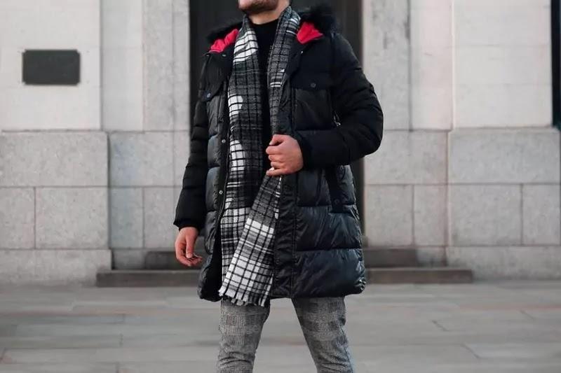 A male in blanket scarf, wearing it stylishly.