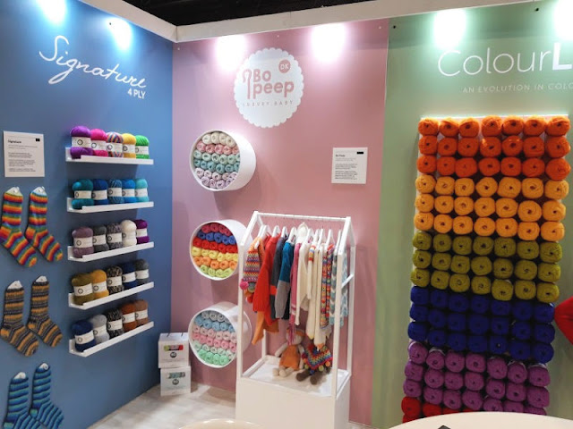 Image shows WYS Signature sock yarn displayed on racks to the left, Bo Peep yarn and garments displayed in the centre and ColourLab yarn in various colours displayed on the right.
