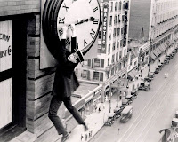 Harold Lloyd dangles over a busy city street hanging onto the hands of a large clock