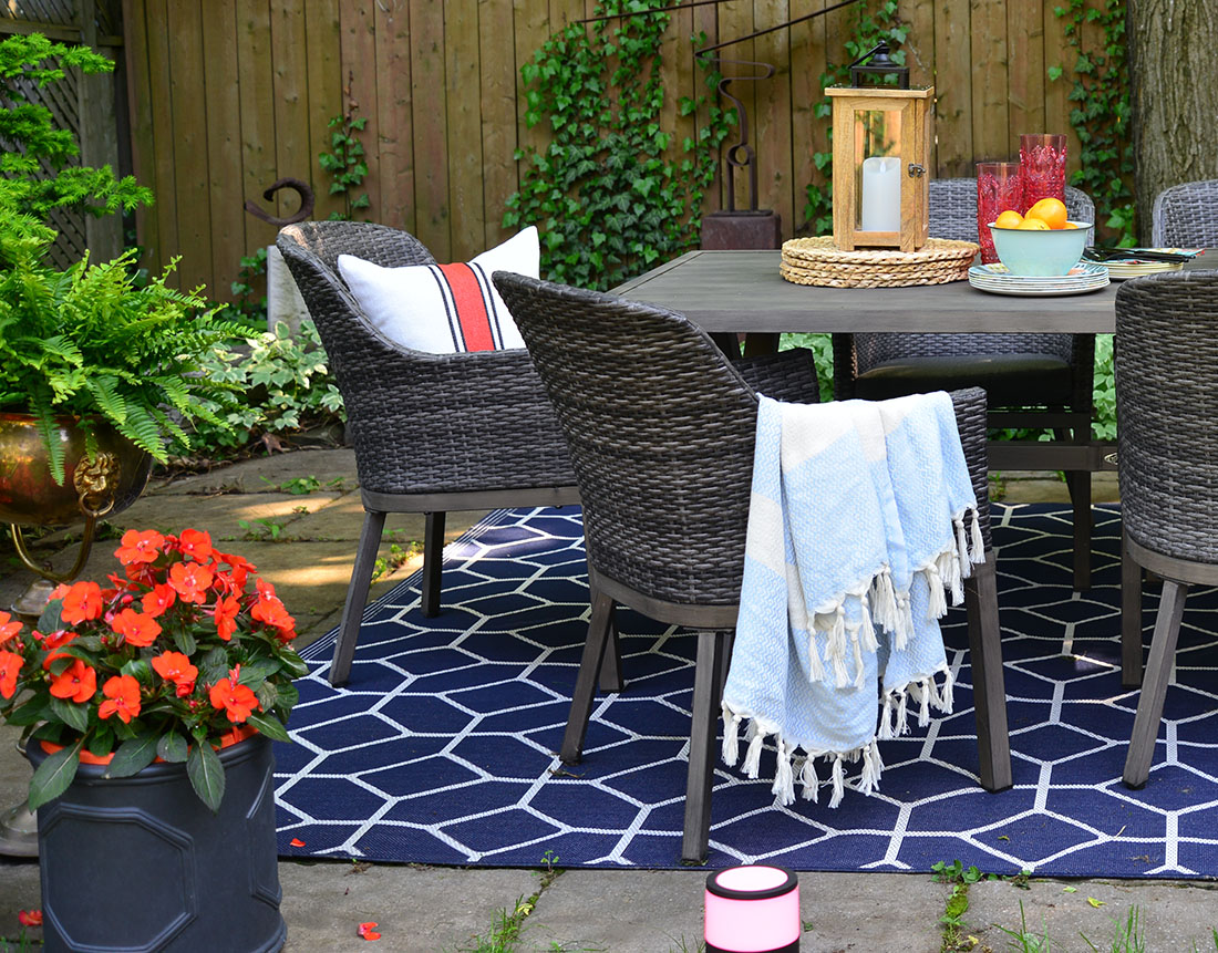 outdoor pillows and throws in basket, outdoor rug, outdoor entertaining, summer party tips