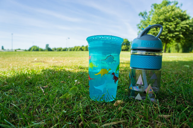 two blue nuby cups on green grass with blue sky in the background