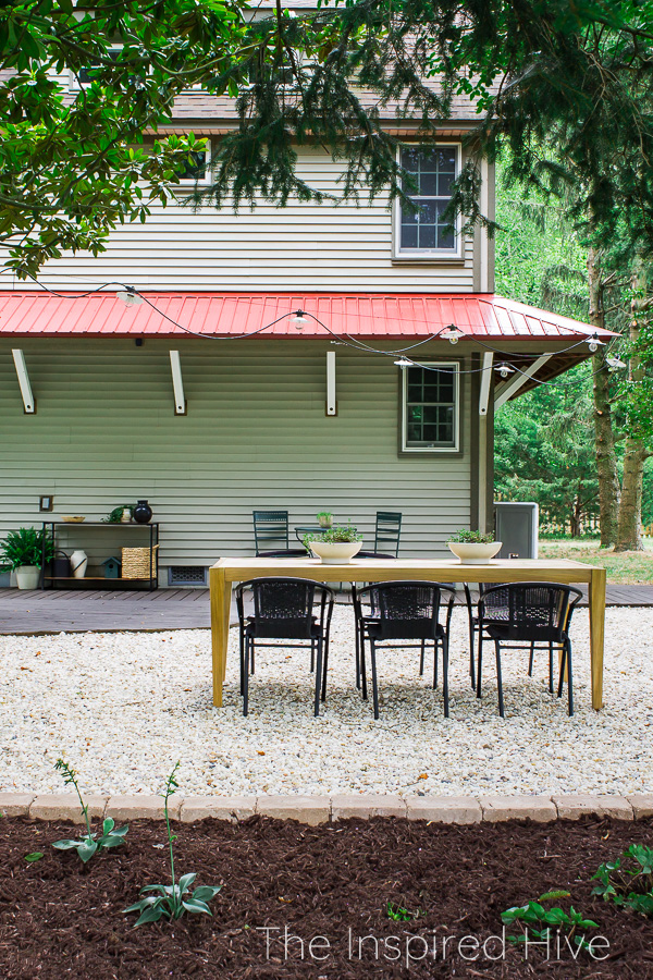 Gravel patio. Red metal roof on farmhouse.