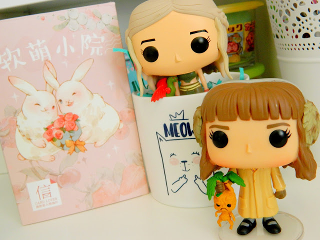 a photo showing two funko pop figures, hermione in herbology class and daenerys with dragon, a pretty pink box filled with postcards and a sweary cat mug