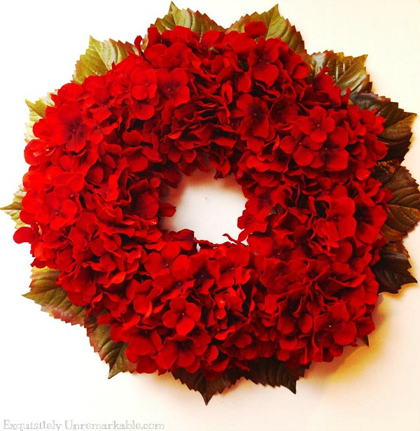 Red Hydrangea Wreath  with green leaves behind