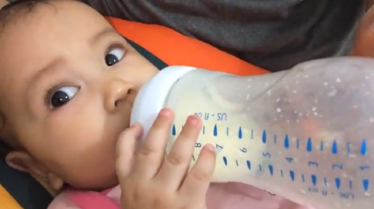 Cute baby girl drinking milk from a bottle
