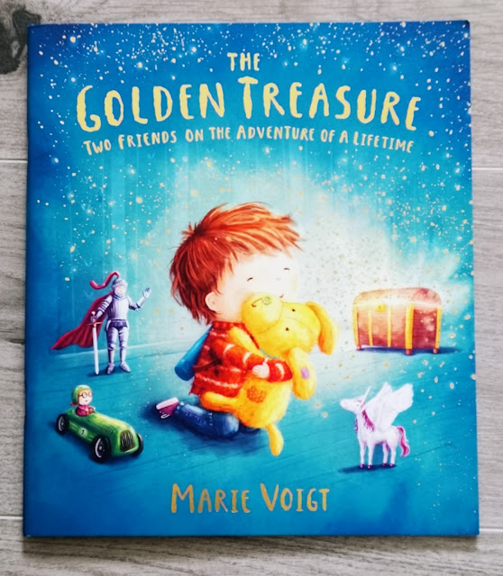 Image of a children's book cover entitled The Golden Treasure by Marie Voigt. Book covers shows a blonde haired boy playing on the floor with a stuffed toy dog surrounded by other toys such as a knight, a race car and a unicorn.