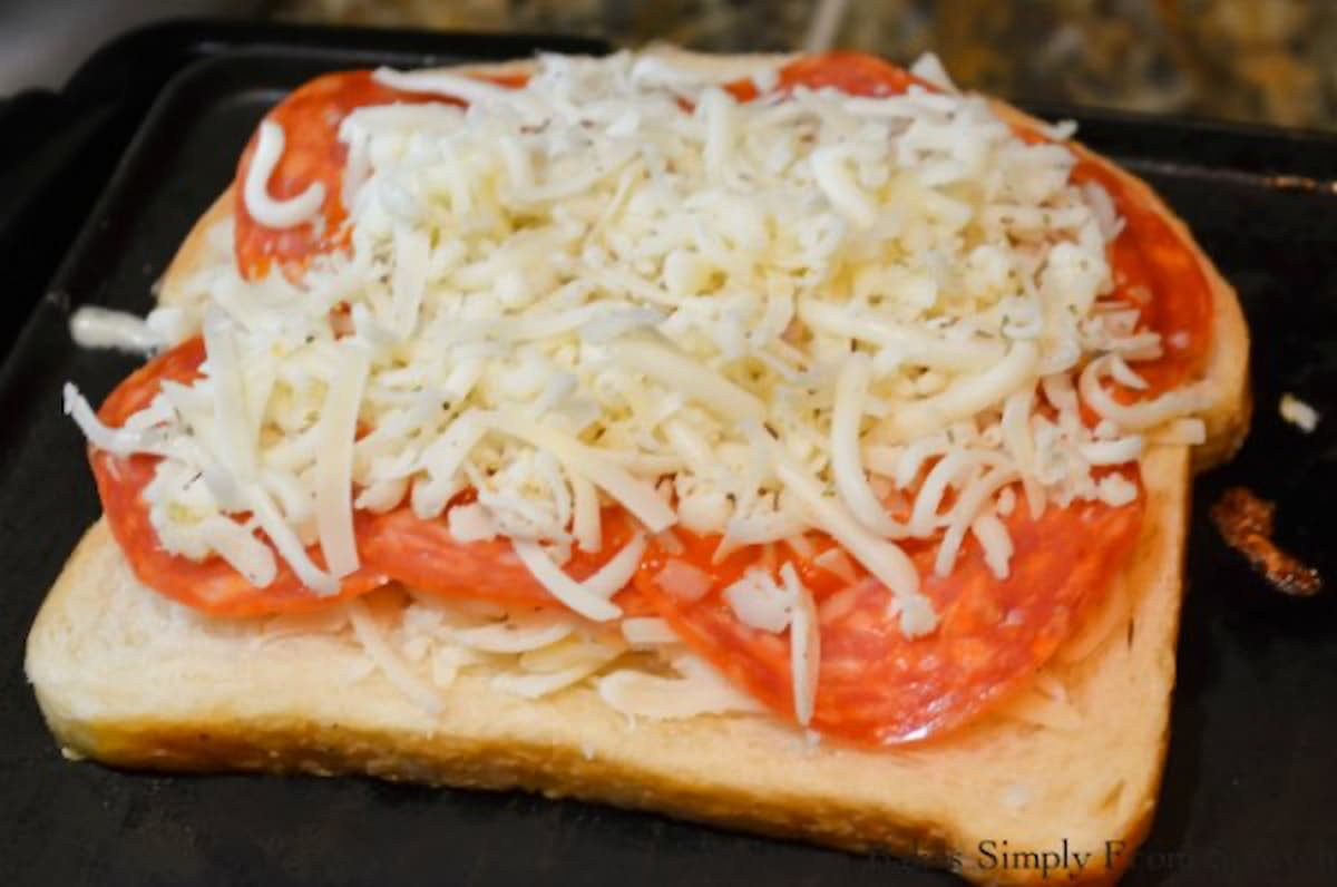 Cheese covering sauce and pepperoni to make a Pepperoni Pizza Grilled Cheese Sandwich.
