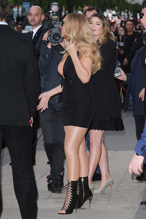 Mariah Carey leaves her hotel in a revealing lowcut black dress in Paris en route to her concert on April 22, 2016. (SplashNews)