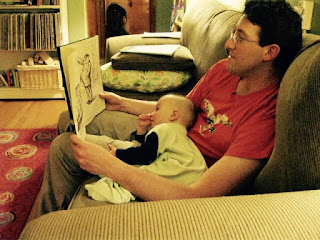 A baby sitting on his dad's lap, reading a book.