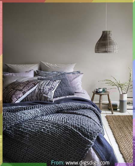 غرفة نوم بجدار رمادي مع غطاء سرير نوم ازرق