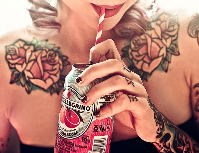 Chica bebiendo refresco con tatuajes en los dedos