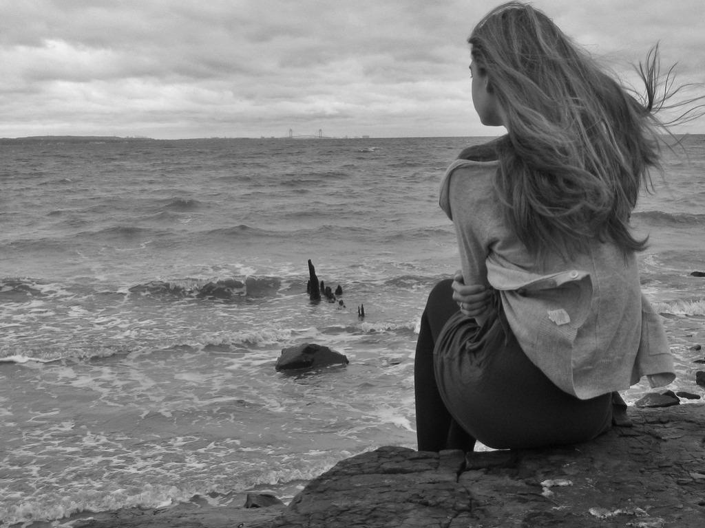 Sad Girl Sitting on Be...