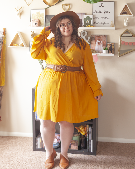 An outfit consisting of a brown panama hat, a lightweight long sleeve yellow faux wrap dress belted with a brown belt and brown d'orsay flats.