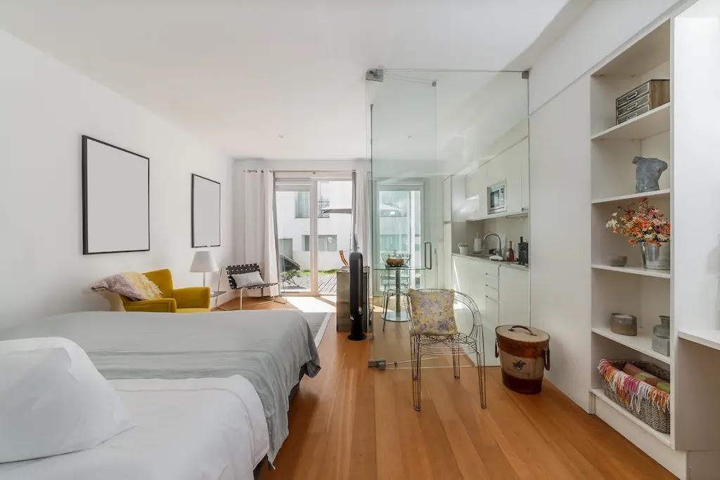 Salón con dormitorio con paredes blancas y paredes de vidrio