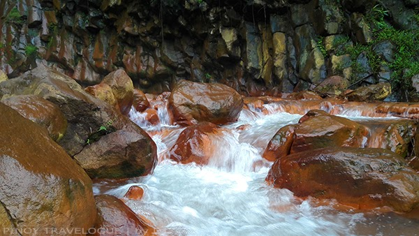 Orange-red rocks of Pulangbato Falls