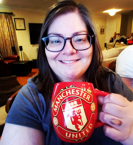 image of me from mid-chest upwards, wearing a grey t-shirt and grey glasses frames, holding a Manchester United mug