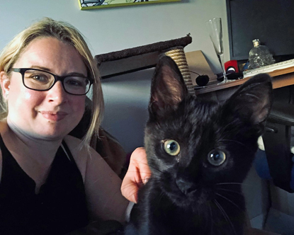blonde woman wearing glasses with black cat