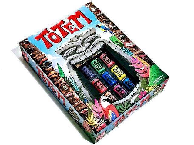 na zdjęciu pudełko gry totem  z czerwonym napisem u góry, kolorowymi rysunkami przedstawiającymi dżunglę, jaskinię, i dwa totemy