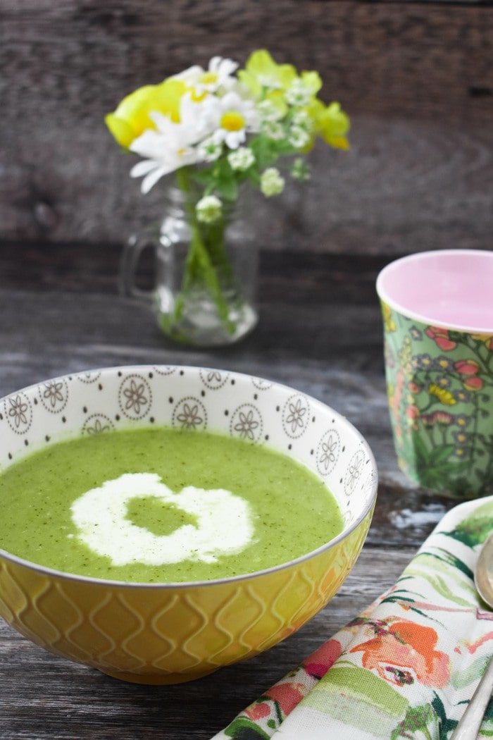 Broccoli soup in a yellow bowl next to a small vase of spring flowers