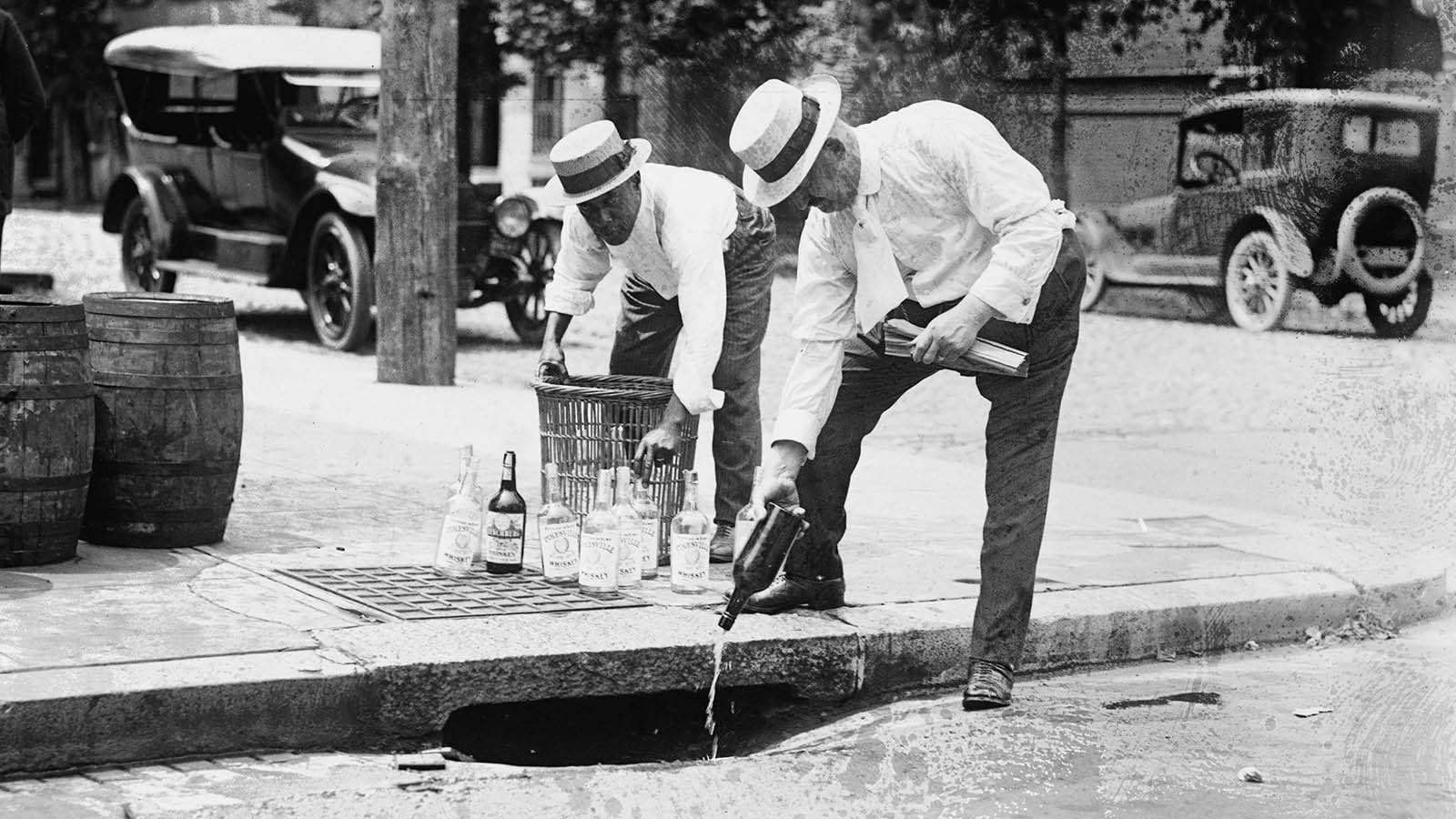 Two men pour alcohol down a drain during prohibition in the United States, c. 1920.