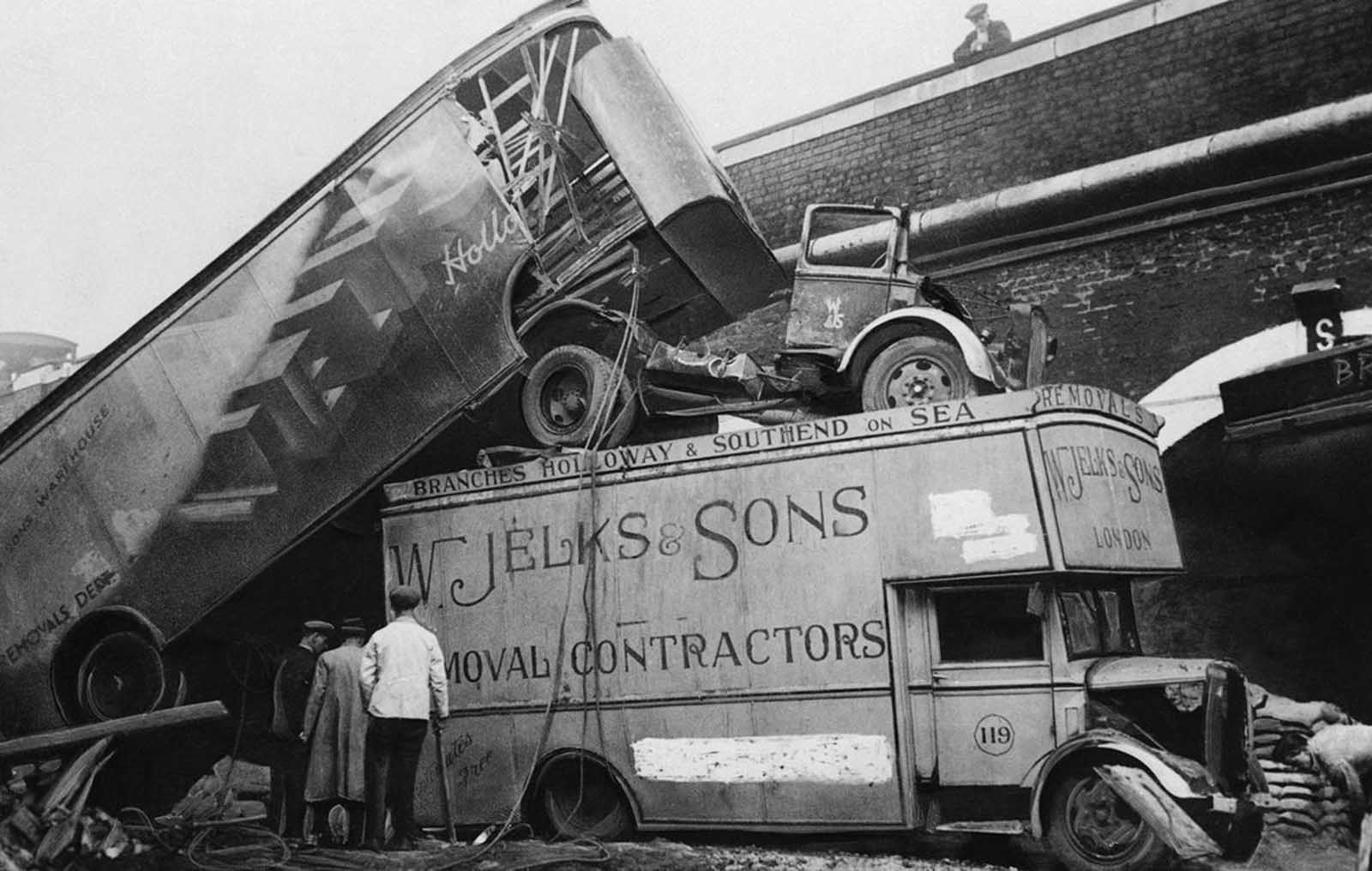 The force of a bomb blast in London piled these furniture vans atop one another in a street after a raid on December 5, 1940.