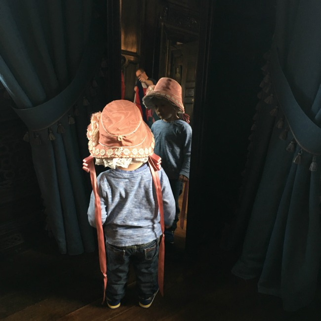 toddler-wearing-bonnet-at-tredegar-house-looking-in-mirror