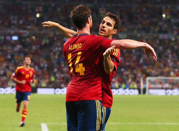 Xabi Alonso of Spain celebrates after scoring the first goal with Cesc Fabregas during the UEFA EURO 2012 quarter final match between Spain and France at Donbass Arena on June 23, 2012 in Donetsk, Ukraine