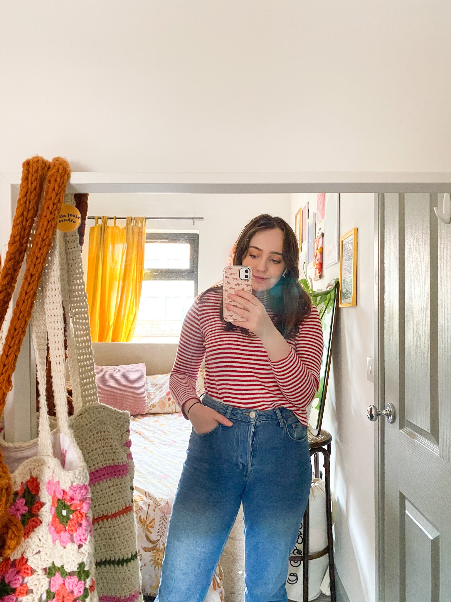 blogger poses for a mirror selfie in bedroom, with bed, plants, prints and curtains in background. Handmade crochet tote bags hang on the corner of the mirror
