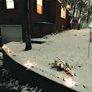 Candles on a wall in front of a house in snow