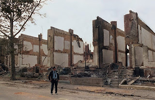 A policeman stands guard on Pine Street in West Philadelphia near the remains of 61 row houses days after they were destroyed by fire on May 13, 1985, when police dropped explosives into a house occupied by members of the radical group MOVE. George Widman/AP