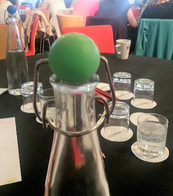Glass Bottle with Green Ball Stopper on a Conference Table
