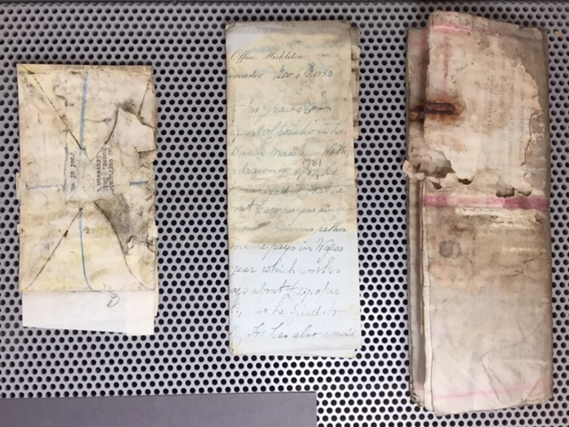 Various documents stained by mould and damp damage.