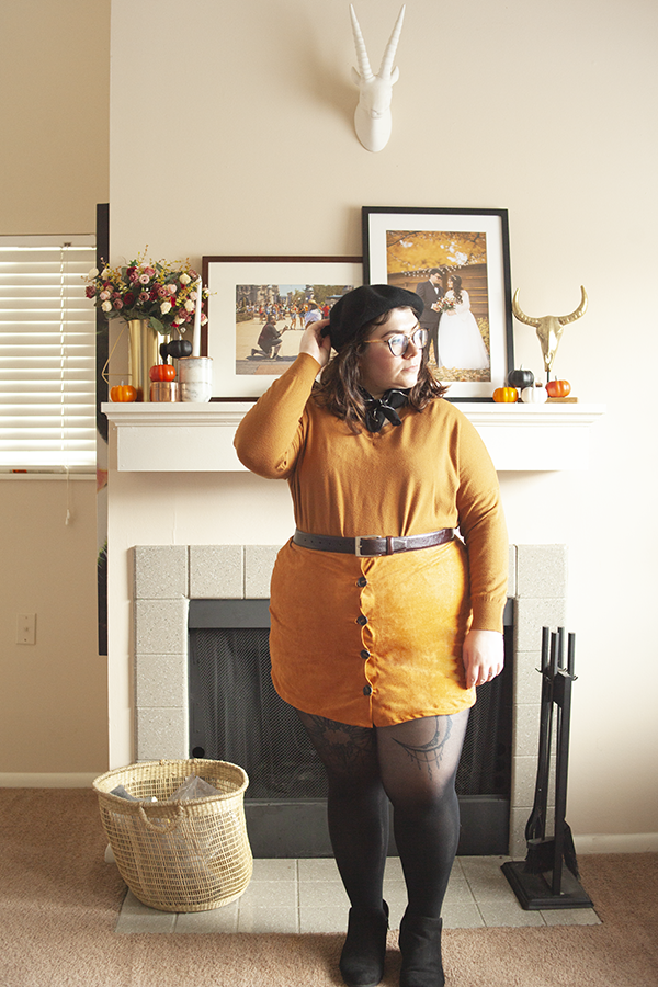 An outfit consisting of a black beret, ochre long sleeve top, brown faux suede button down mini skirt, and black ankle boots.