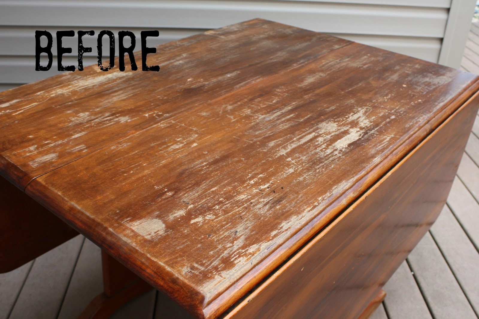Solid wood drop leaf table with severe damage to finish