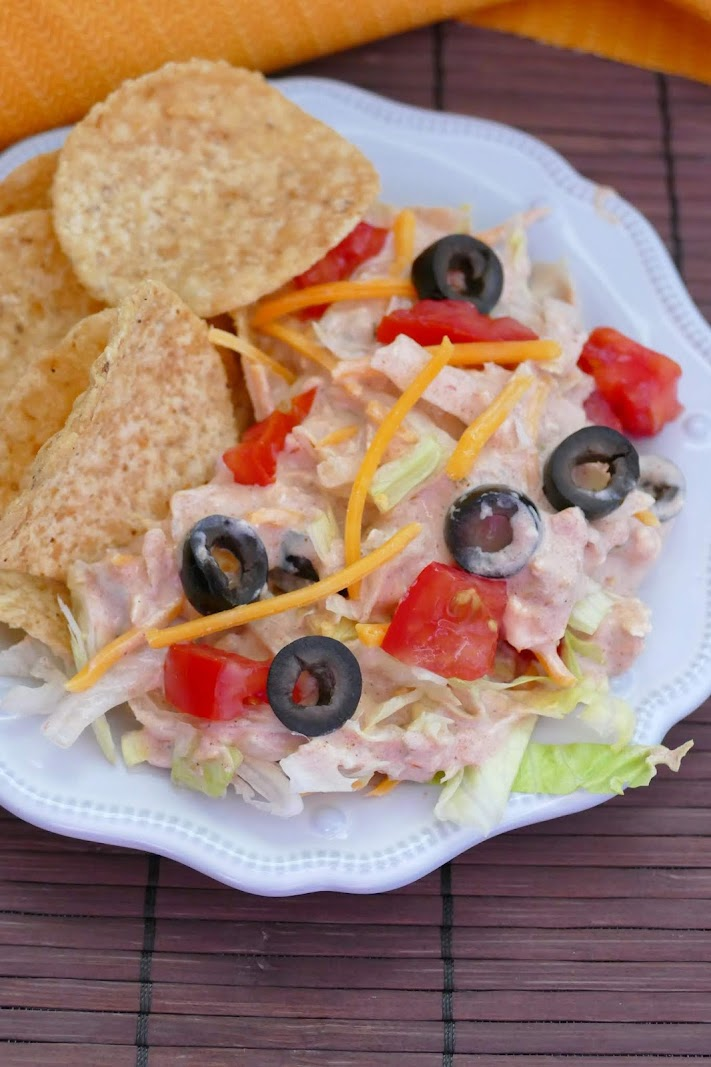This easy meatless Mexican taco dip is layered with a creamy salsa mixture, lettuce, cheese, tomatoes and black olives is absolutely amazing and is great for any game day party, potluck, taco night or picnic! Serve with tortilla chips!