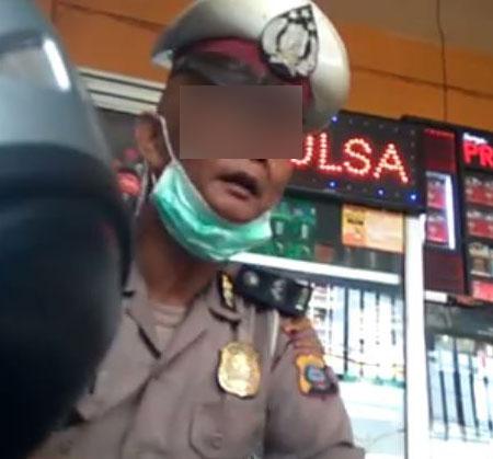 Oknum polisi yang meminta uang kepada pengendara sepedamotor.