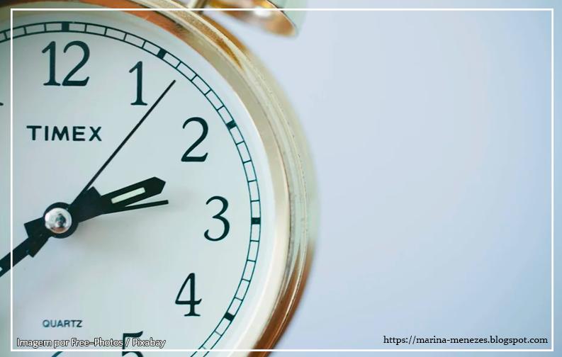A imagem mostra um relógio na parte esquerda da foto, parcialmente oculto pelo ângulo da foto. A imagem mostra os ponteiros apontando para duas horas