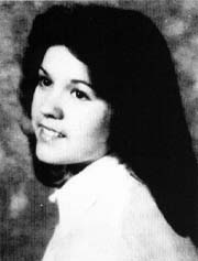 High school yearbook photo of a finely-featured white girl with thick dark hair and dark eyes
