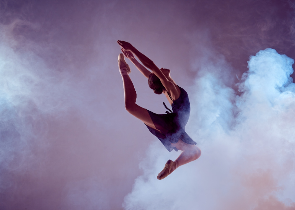 Ballet dancer jumping through smoke.