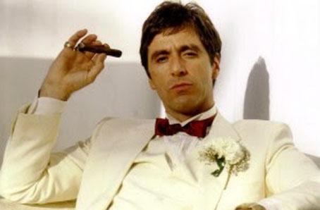 """Cette photo, tirée du film Scarface réalisé par Brian de Palma en 1983, montre Tony Montana, interprété magistralement par Al Pacino, en costume blanc, assis avec un cigare. Cette image accompagne le poème du Marginal Magnifique """"The world is yours"""", célèbre phrase du film. Dans ce poème, Le Marginal Magnifique explique avec humour et en faisant allusions à des moments forts et des scènes cultes du film, comme le passage où Tony risque de se faire sauvagement assassiner dans une salle de bains à coups de tronçonneuse par des trafiquants récalcitrants, que cette phrase n'a pas de réalité dans la vraie vie. En effet, contrairement à ce qui ce passe dans les films, au cinéma, la vie met est souvent dure, n'est pas un rêve. Ce poème donne également une leçon à tous les jeunes qui rêvent d'une destin à la façon de Tony Montana dans Scarface en leur expliquant qu'en suivant le même chemin ils risquent davantage de souffrir et de traverser des épreuves atroces avant de finir misérablement et prématurément que d'avoir une vie riche et voluptueuse pavée de moments d'extase."""