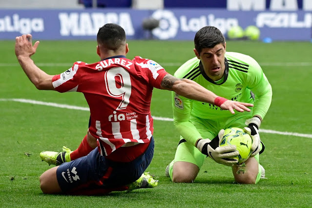 Real Madrid goal keeper Thiabut Courtois stops Atletico Madrid forward Luis Suarez